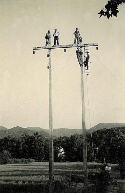 hommes installant des câbles electriques en haut de poteaux en bois